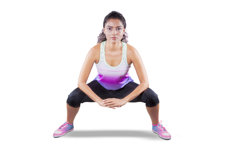 Picture of a young woman doing squat exercise in the studio, isolated on white background