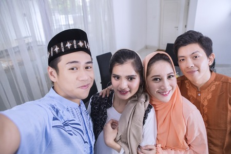 Young Muslim people taking a selfie photo together in the dining room. Shot at home