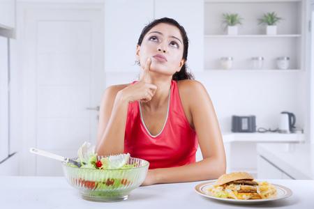 Joven india pensando en elegir una ensalada de verduras o una hamburguesa mientras está sentado en la cocina. Disparo en casa