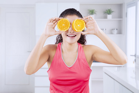 Image of a happy Indian woman covering her eyes with two slices of orange in the kitchen. Shot at home Imagens - 122085609