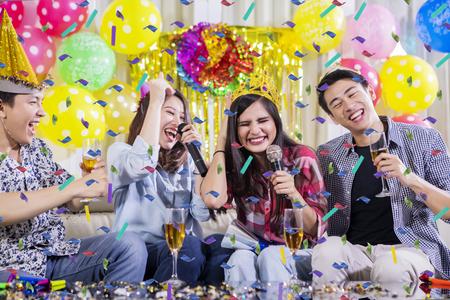 Dos parejas jóvenes cantando juntos mientras beben champán en una fiesta de cumpleaños Foto de archivo