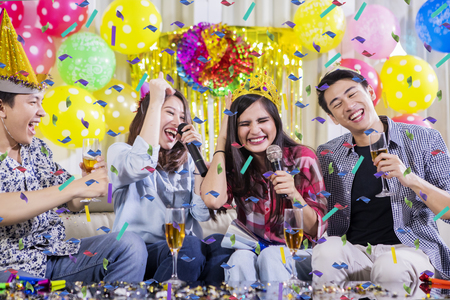 Two young couples singing together while drinking champagne at a birthday party