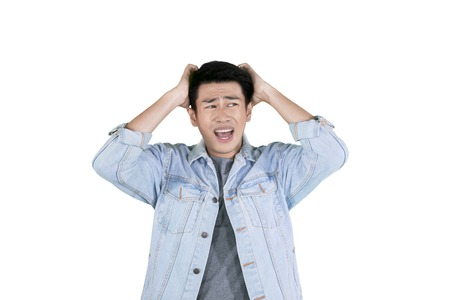 Young Asian man having headache while holding his head and standing in the studio, isolated on white background Stockfoto