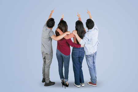 Rear view of four young people hugging each other while pointing something together in the studio