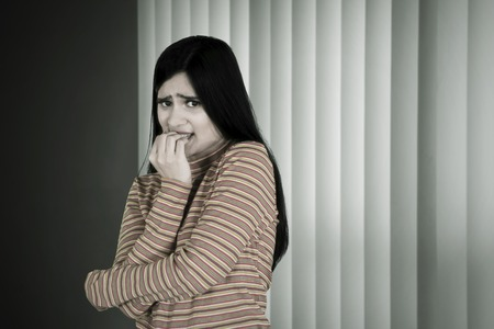 Young woman looks afraid while biting her finger and standing in the dark room near the window