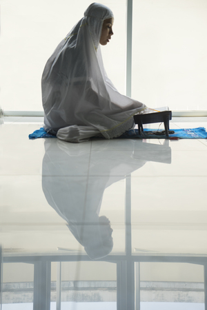 Picture of devout Muslim woman reading Quran near the window while wearing islamic clothes at home