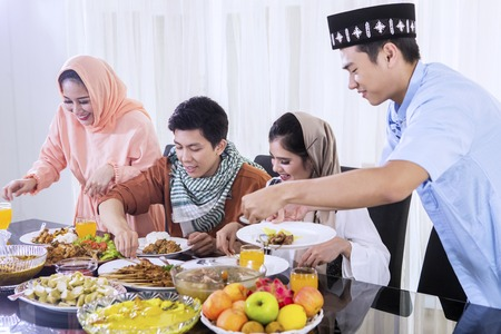 Group of young Asian people taking foods and preparing for breaks the fast together in the dining room. Shot at home Stock Photo