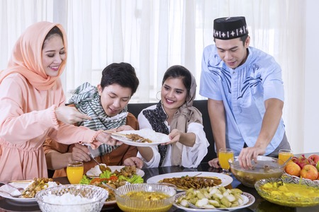 Group of happy young people taking foods and preparing for breaks the fast together in the dining room. Shot at home Stock Photo