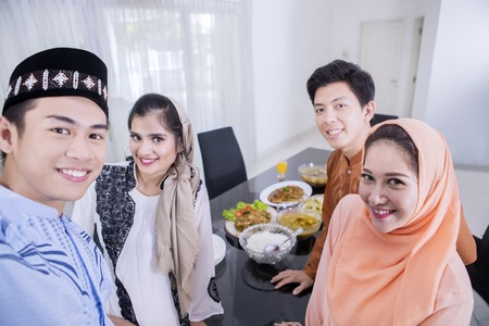Group of young Muslim people takes a selfie photo together in the dining room. Shot at home