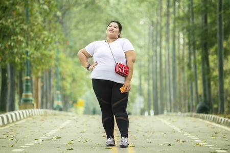 Picture of fat woman looks confident while standing on the road Stock Photo - 122769388