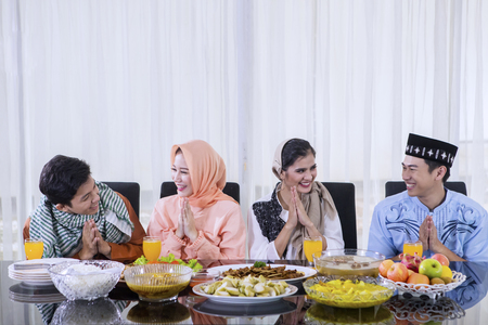 Group of cheerful young people congratulating Eid Mubarak before eating together in the dining room