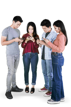 Full length of four young people using mobile phone while standing together in the studio