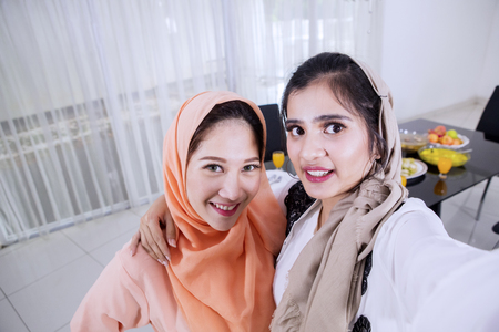 Picture of two women taking selfie photos together before breaking the fast in the kitchen