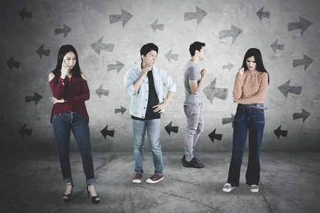 Group of confused young people thinking something with left and right arrows