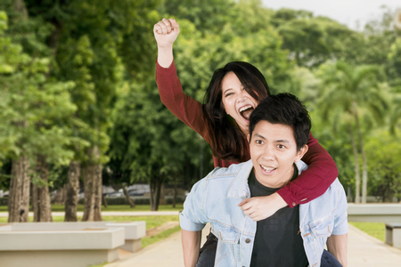 Image of a young Asian man looks happy while giving his girlfriend piggyback ride in the park