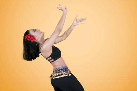 Side view of beautiful woman doing belly dance in the studio with orange color
