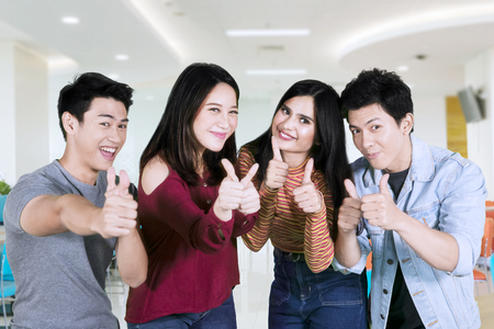 Group of cheerful college student showing ok sign together while looking at camera 版權商用圖片