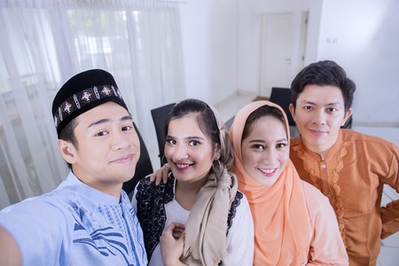 Two Muslim couples taking a selfie photo together in the dining room. Shot at home 版權商用圖片