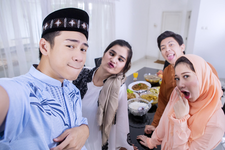 Group of cheerful Muslim people takes a selfie photo together in the dining room. Shot at home