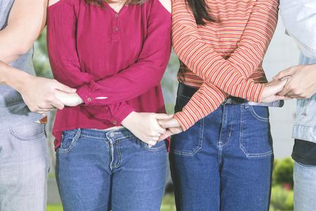 Nahaufnahme von jungen Leuten, die sich Händchen halten, um Einheit und Teamwork im Park zu zeigen Standard-Bild