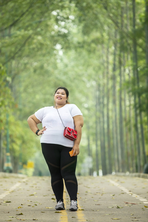 Full length of obese woman looks confident while standing on the road Фото со стока - 122767917