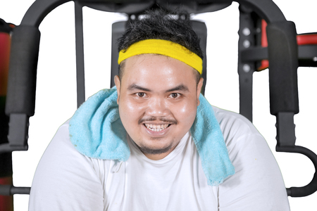 Close up of young fat man smiling at the camera while sitting on the exercise machine, isolated on white Stock Photo
