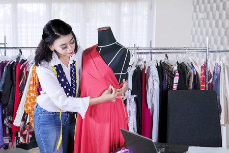 Picture of female dressmaker adjusting a dress on a mannequin while working in the workplace 版權商用圖片