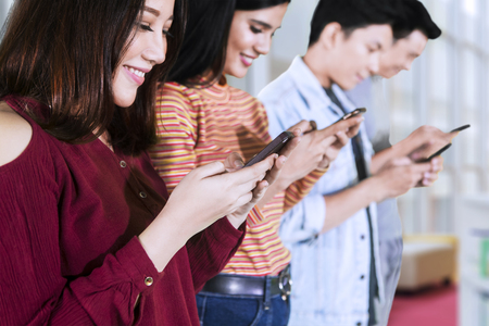 Close up of four college students using smartphones to browse internet in the campus