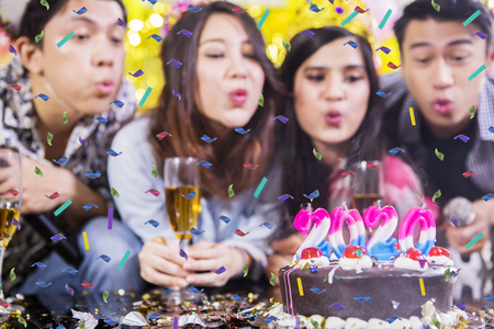 Group of young people blowing candles with numbers 2020 on the birthday cake Stockfoto