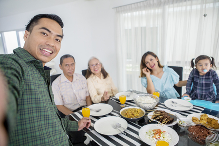 Young man taking photo with his family in dining table while eating together