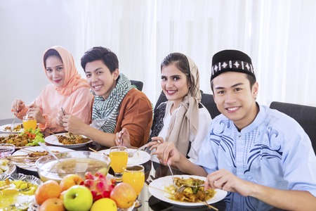 Group of young Muslim people enjoying meals at breaks the fast together in dining table. Shot at home