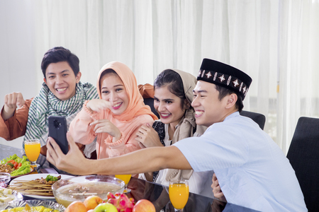 Group of young people making a video call by using a smartphone while breaking the fast together at home Imagens - 122963831