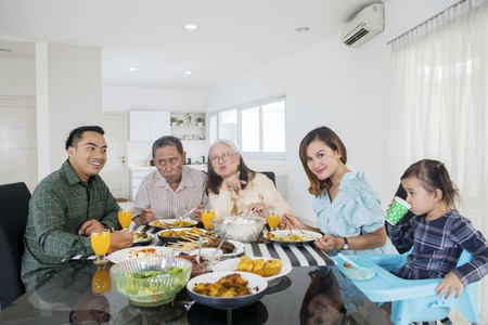 Picture of extended family looks happy while eating meals together at the dining table. Shot at home