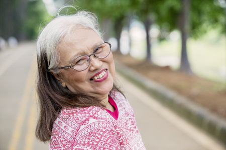 Close up of elderly woman smiling at the camera while standing on the road. Shot at park