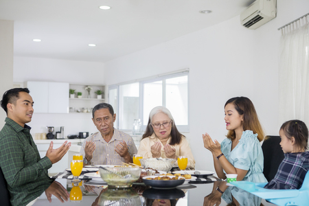 Picture of Asian extended family praying together before having meals at home. Shot in dining table