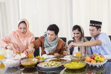 Picture of four people taking foods during breaks the fast together in the dining room. Shot at home