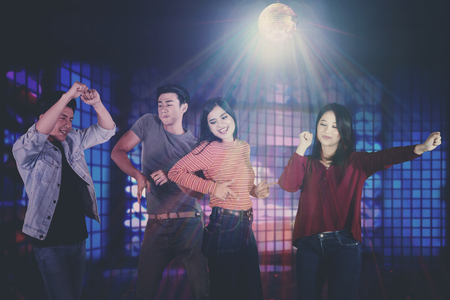 Group of young Asian people enjoying a party while dancing together in the nightclub