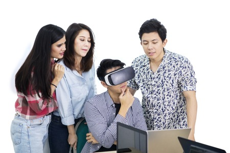 Image of pensive young man using a virtual reality goggles while working with his partners in the studio