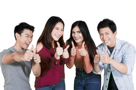 Group of college students looks happy while showing thumbs up in the studio, isolated on white background