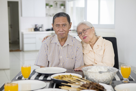 Picture of romantic elderly couple looking at the camera while sitting in front of the dining table 版權商用圖片