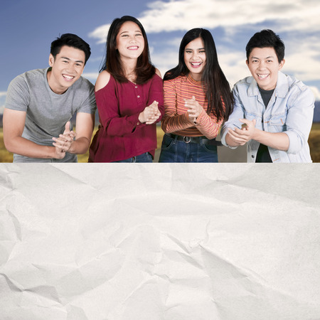 Group of happy college students applauding at the camera while showing blank crumpled paper Imagens