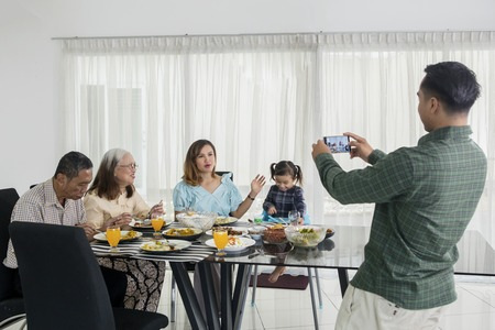 Young man using a smartphone to taking photo his family in dining table while eating together