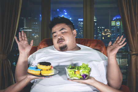 Picture of fat man choosing a vegetable salad or donuts with confused expression in the apartment