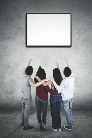 Rear view of four young people hugging each other while pointing at an empty whiteboard