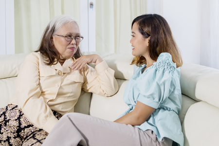 Picture of Asian woman speaking with her mother while sitting together on the couch. Shot at home 免版税图像