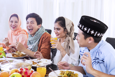Group of young happy people enjoying meals at breaks the fast together in dining table. Shot at home