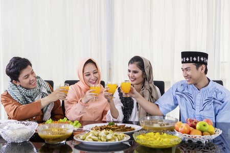 Group of young happy people toasting and drinking orange syrup before breaks the fast together in the dining room
