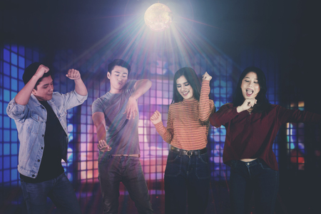 Group of young Asian people dancing together and having fun in the nightclub 스톡 콘텐츠