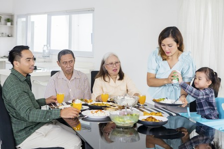 Picture of big family eating meals together at the dining table. Shot at home Imagens