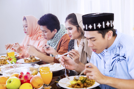 Group of young people enjoying meals at breaks the fast together in dining table